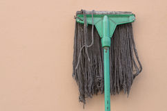 A mop lying against a wall. Royalty Free Stock Image