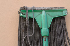 A mop lying against a wall. Royalty Free Stock Photos