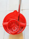 Mop in red bucket with washing water Royalty Free Stock Images