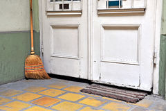 Mop at the white wooden door on floor Stock Photos