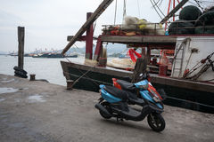 Moped and fishing boat in the fishing port in Macau. Royalty Free Stock Photos