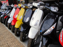 Moped motorbikes in a row. Close up of a row of motor bikes for sale or rental Stock Photo