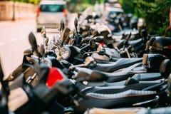 Moped motorcykelsparkcyklar som parkeras i rad i stadsgata Royaltyfria Bilder