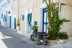 The moped. The old moped parked next to the door of residential house, Mahdia, Tunisia Royalty Free Stock Photo