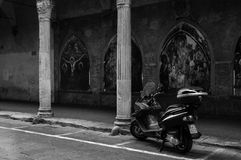 Moped parked on a street with religious murals Stock Image