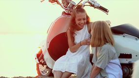 The moped the sea. Two little girls have fun on the beach at water. Two sisters enjoy weather on the beach. On this video you can see as the close-knit family stock footage