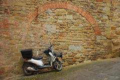 Moped on Sloped Road. A moped parked next to an old wall on a sloped street in Tuscany Royalty Free Stock Photos