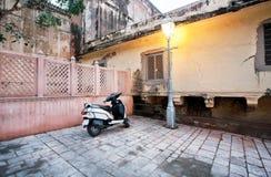 Moped som parkeras nära en gatalampa Royaltyfria Bilder