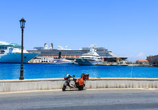 Moped on street and cruise ships at the port of Rhodes, Greece Royalty Free Stock Images