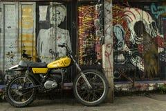 Mopeden som parkerades på gatan med grafitti, täckte väggar royaltyfri foto