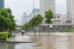 Mopedridning på översvämmad trottoar Royaltyfri Foto