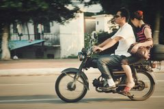 Guangzhou, China - July 22, 2018: Man and woman riding a motorcycle down the street in Guangzhou stock image