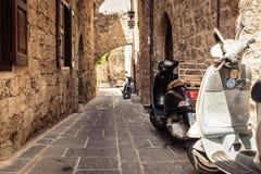 Mopedsparkcyklar parkeras nära väggen på den smala gatan av den Rhodes staden på den Rhodes ön, Grekland Arkivfoto