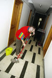 Mopping the hallway. Young maid in colorful shirt mopping the hallway Royalty Free Stock Photography