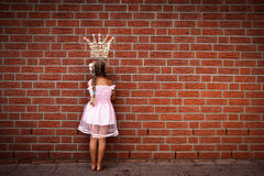 Moping princess. A moping princess in front of a wall with a sketch of her crown on it Royalty Free Stock Image