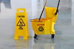 Mopp, Wanne und Achtung-nasser Fußboden Lizenzfreie Stockfotos