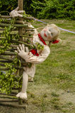 Moppet. A rag doll in a wicker fence on the background of nature Stock Image