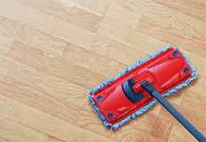 Mopping. Cleaning laminate. Red mop on hardwood floors Stock Image