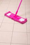Mopping tile floor in light bathroom Royalty Free Stock Photos
