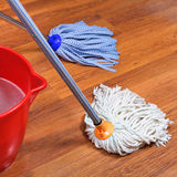 Mopping of wood floors by two mops. And red bucket Stock Images