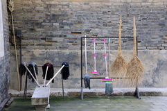 Mops and Brooms. A variety of different cleaning mops and brooms hanging up to dry in China Royalty Free Stock Image