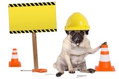 Mopshund med den gula hjälmen och kotten för konstruktörarbetarsäkerhet, plus varningstecken på träpol Royaltyfria Foton