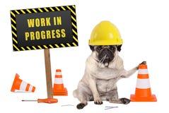 Mopshund med det pågående tecknet för konstruktörsäkerhetshjälm och för guling- och svartarbete på träpol Arkivfoto