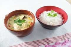 Moqueca de los pescados y de los paprikas, brasileño de la comida, servido con el arroz blanco, en una tabla de madera foto de archivo libre de regalías