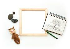Moquerie étendue plate, vue supérieure, cadre en bois, écureuil de jouet, crayon, bloc-notes, pierres Disposition intérieure, photos stock