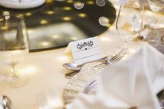 Moquerie blanche de label de papier blanc avec l'art d'ornement pour le nom sur la table de dîner avec le fond trouble de bokeh image libre de droits