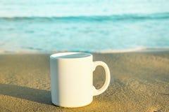Moquerie de blanc vers le haut de tasse avec l'espace vide pour le texte d'illustration se tenant sur le sable de plage Mer de bl Photographie stock libre de droits