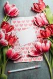 Moquerie de carte de voeux de printemps avec de jolies tulipes, coeurs, carte vierge blanche et stylo, vue supérieure, cadre Disp Photos libres de droits