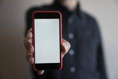Moquerie de téléphone de couleur rouge de mains de maquette vers le haut de l'affichage de participation d'écran blan Photos stock