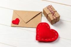 Moquerie de vacances : boîte-cadeau, coeur rouge et papier blanc dans l'enveloppe brune sur le fond en bois blanc Concept d'amour Image libre de droits