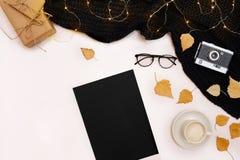 Moquerie romantique d'automne  Feuille de papier noir, feuilles jaunes et oranges, crayons, tasse de cappuccino et vieil appareil Photographie stock libre de droits