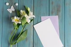 Moquerie vers le haut de papier blanc, d'enveloppe de courrier sur un fond en bois bleu avec les fleurs blanches naturelles et de photographie stock