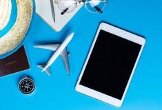 Moquerie vide de comprimé avec des accessoires de voyage sur le bleu Image libre de droits