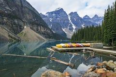 Morän sjö och färgrika kanoter i den Banff nationalparken, Alberta, Kanada Arkivfoton