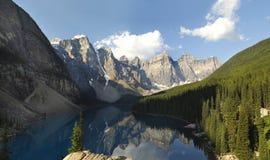 Morän sjö som reflekterar de omgeende bergen arkivfoto