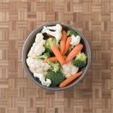Morötter, broccoli och blomkålen i en stengods bowlar royaltyfri bild