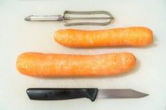 Morötter, en kniv och en grönsakskalare på en vit skärbräda Arkivfoto