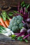 Morötter för nya grönsaker, rödbetor, broccoli, gräslökar på trä Royaltyfria Foton