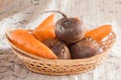 Morötter och beta i korgen Arkivfoto