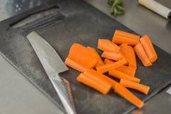 Morötter och en bitande kniv Arkivbild