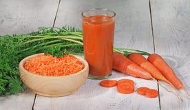 Morötter och morotfruktsaft Arkivbild