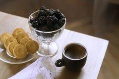 Mora en un florero, aún-vida del desayuno de la mañana con café, mora y galletas Imagen de archivo libre de regalías