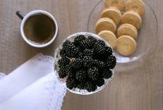 Mora en un florero, aún-vida del desayuno de la mañana con café, mora y galletas, visión superior Foto de archivo libre de regalías