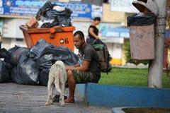 Morador da rua de Brasil assentado ao lado dos sacos do balde do lixo e de lixo Imagens de Stock