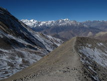 Moraine and high mountains on the way from Thorung La Pass to Muktinath Stock Images