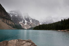 Moraine Lake, Canada. Snow-cowered mountains and Moraine Lake in Banff National Park, Canada covered in clouds Stock Photo
